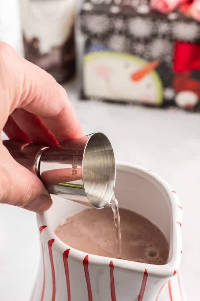 adicionar uma dose de vodka com sabor de chantilly à mistura de cacau quente em uma caneca branca