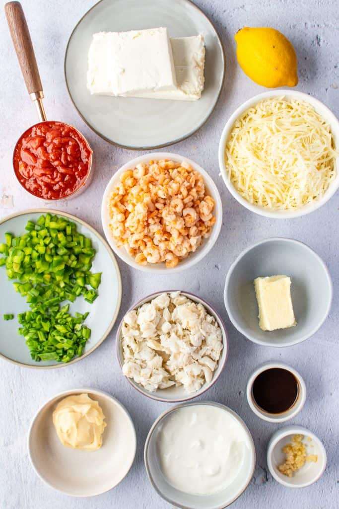 cream cheese, sour cream, mayonnaise, unsalted butter, Worcestershire sauce, a fresh lemon, minced garlic, cocktail sauce, lump crab meat, tiny shrimp, shredded Mozzarella cheese, sliced green onions, diced green pepper