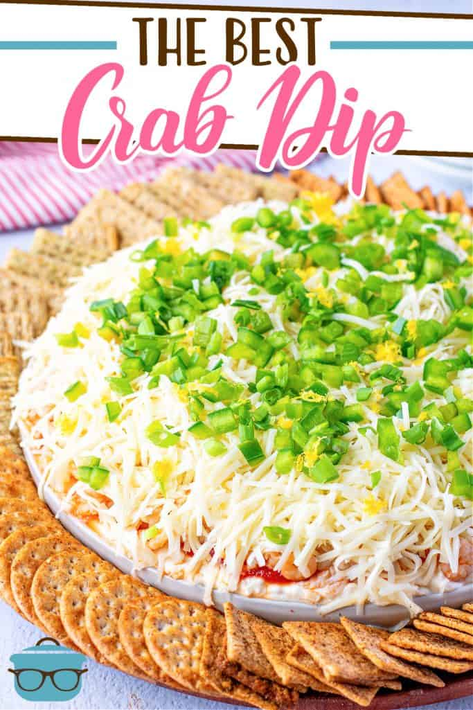 The Best Crab Dip recipe from The Country Cook, dip shown on a round white platter, topped with sliced green onions with crackers arranged in a circle around the dip