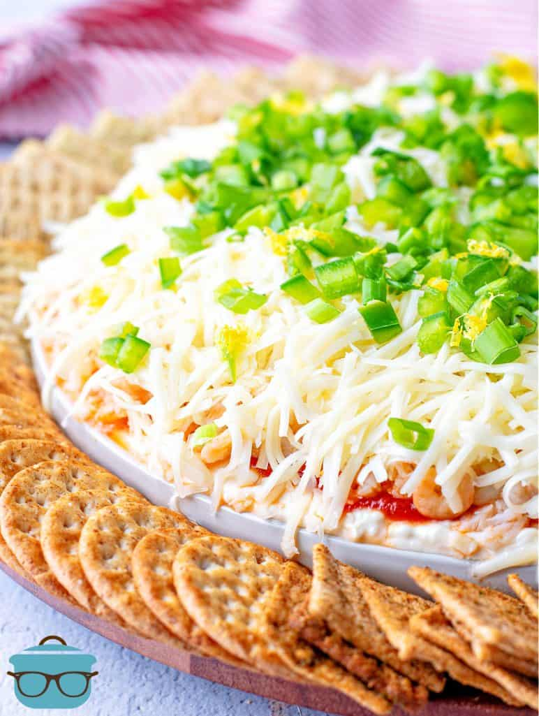 closeup photo of seafood dip topped with sliced green onions and crackers surrounding the platter in a circle