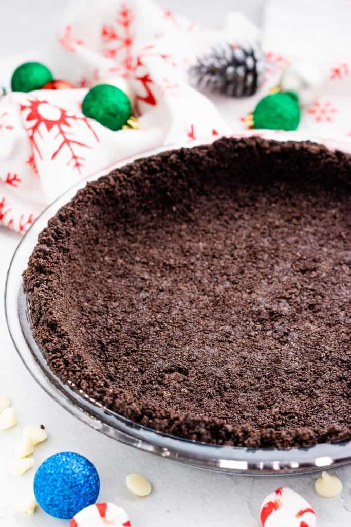 Oreo Cookie pie crust in a clear round pie pan with small Christmas decorations in the background