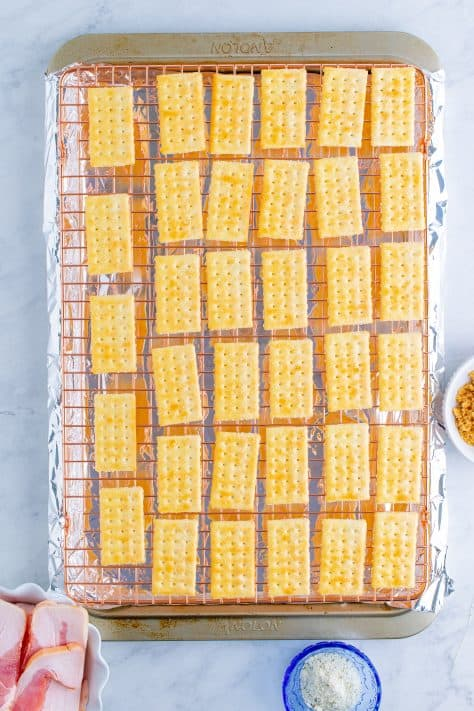 Crackers lined up on wire rack over baking sheet