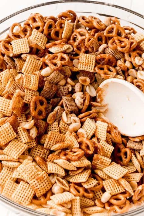 Butter and spices added to Chex mix being stirred