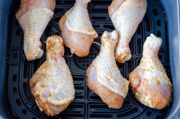 Seasoned uncooked drumsticks in air fryer