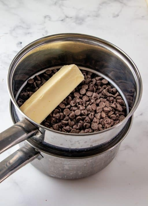 Chocolate chips and butter in double boiler for sauce for Chocolate Covered Strawberry Bread Pudding