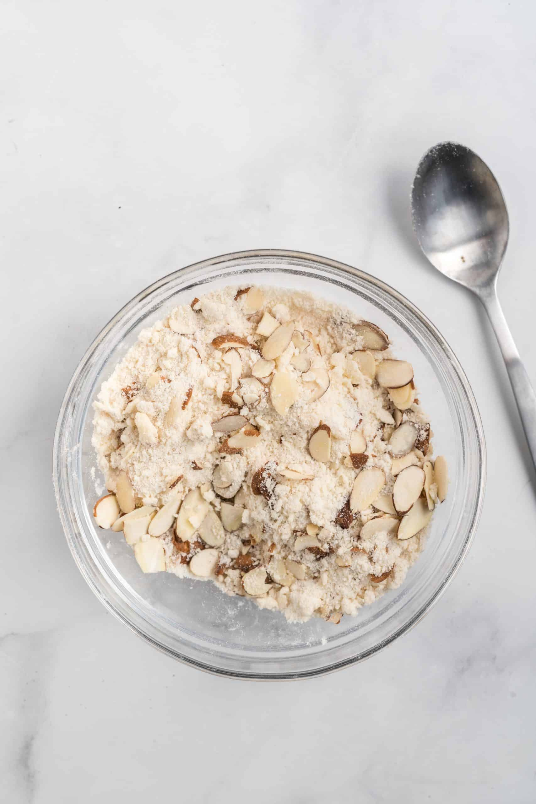 streusel ingredients in a small clear bowl with a silver spoon on the side.