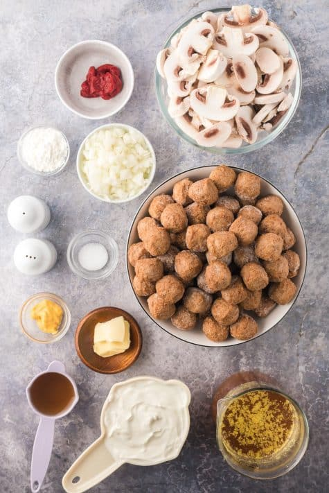 Ingredients needed to make Crock Pot Meatball Stroganoff: unsalted butter, onion, sliced mushrooms, cooked frozen meatballs, beef broth, tomato paste, mustard, sour cream, cornstarch, water