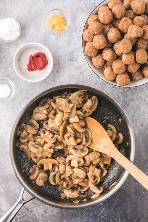 Sautéed mushrooms in pan being stirred