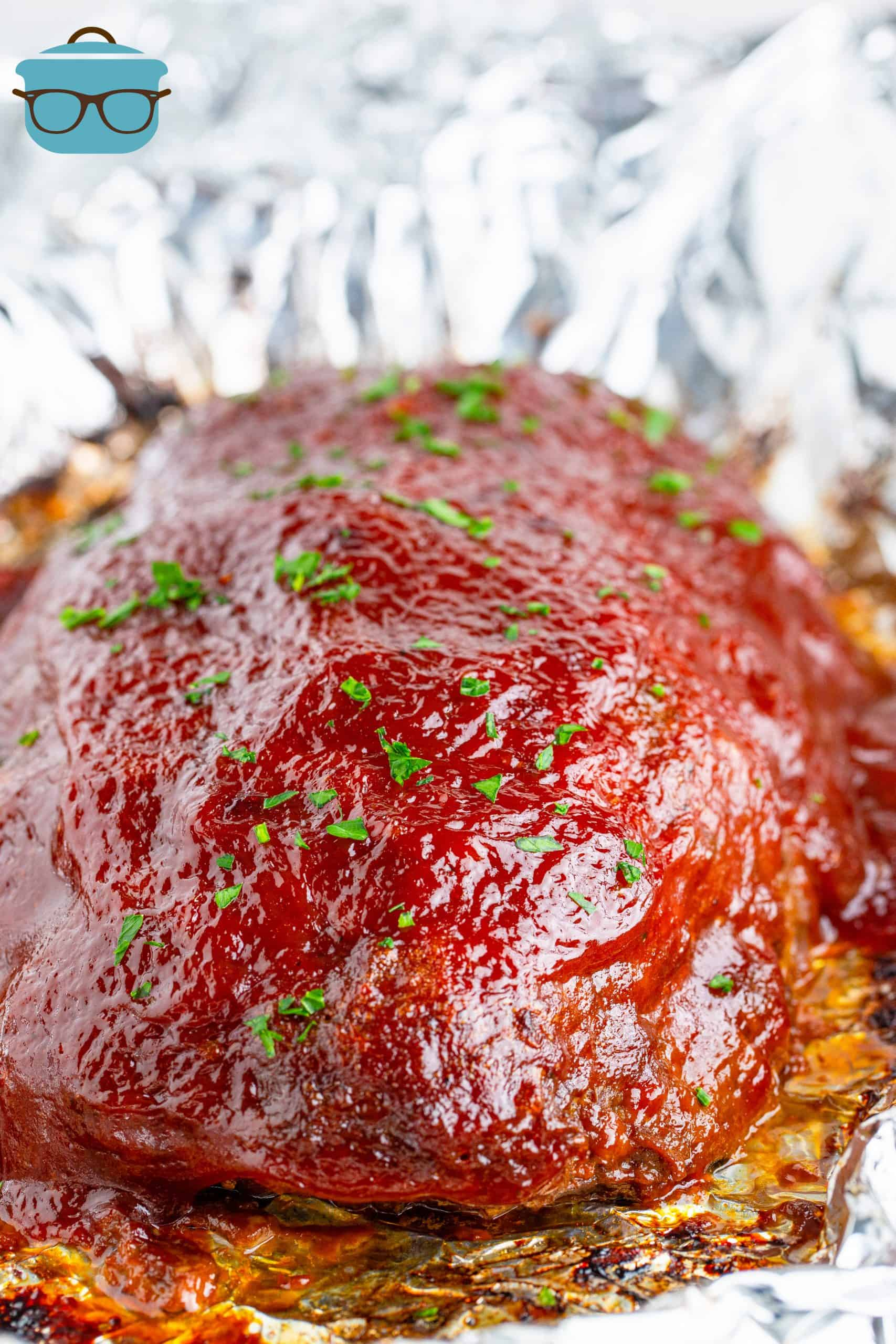 Finished meatloaf on foil topped with parsley