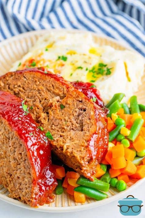Duas fatias de bolo de carne em cima de uma mistura de vegetais e batatas