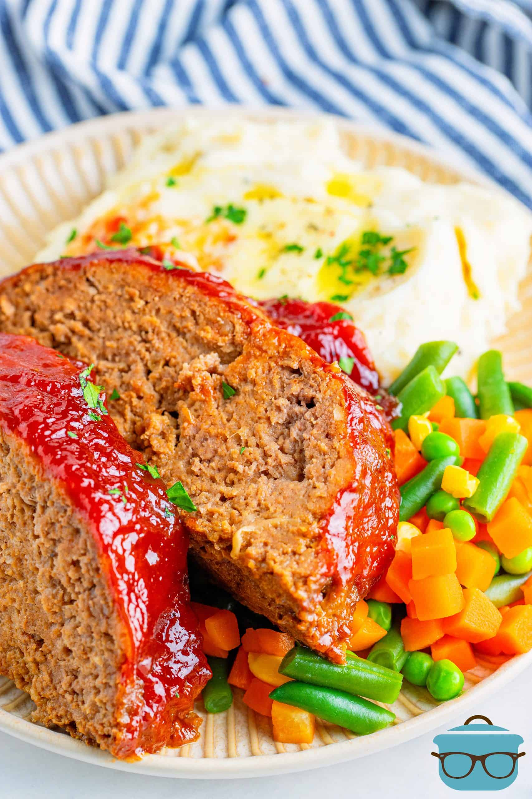 Two slices of meatloaf on top of mixed vegetables and potatoes