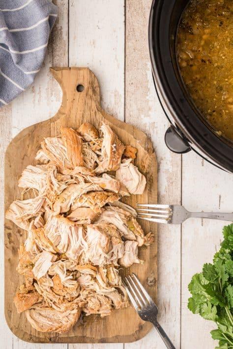 Chicken shredded on cutting board