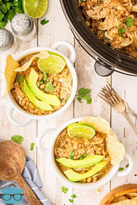Overhead of two bowls of Crock Pot White Chicken Chili topped with avocado, limes and chips