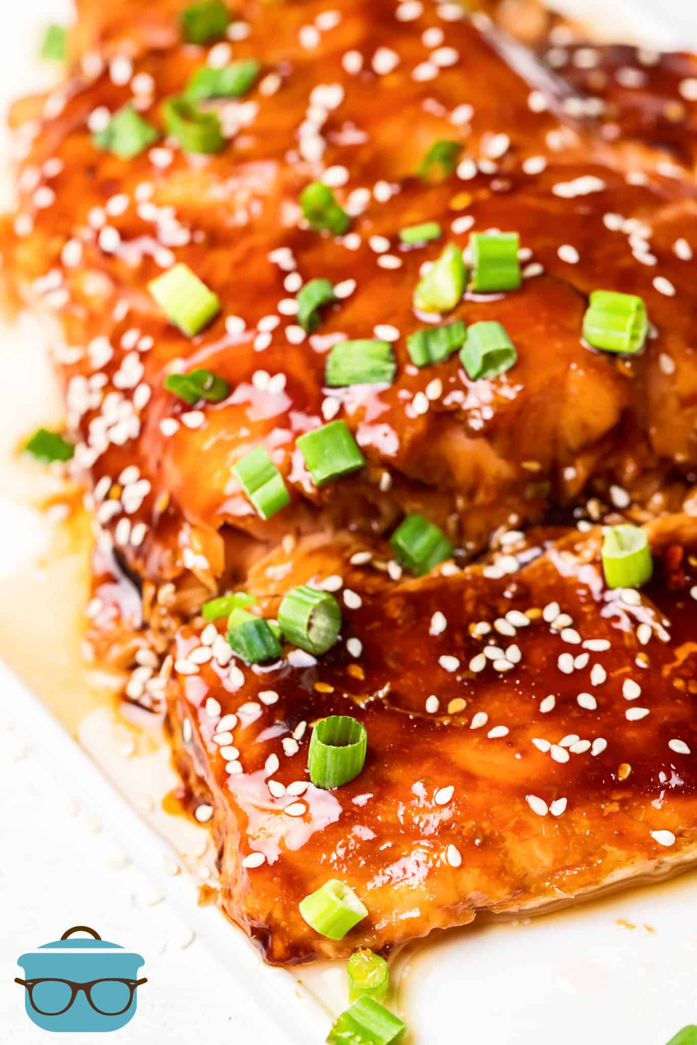 Close up of salmon cut, glazed and topped with sesame seeds and green onions