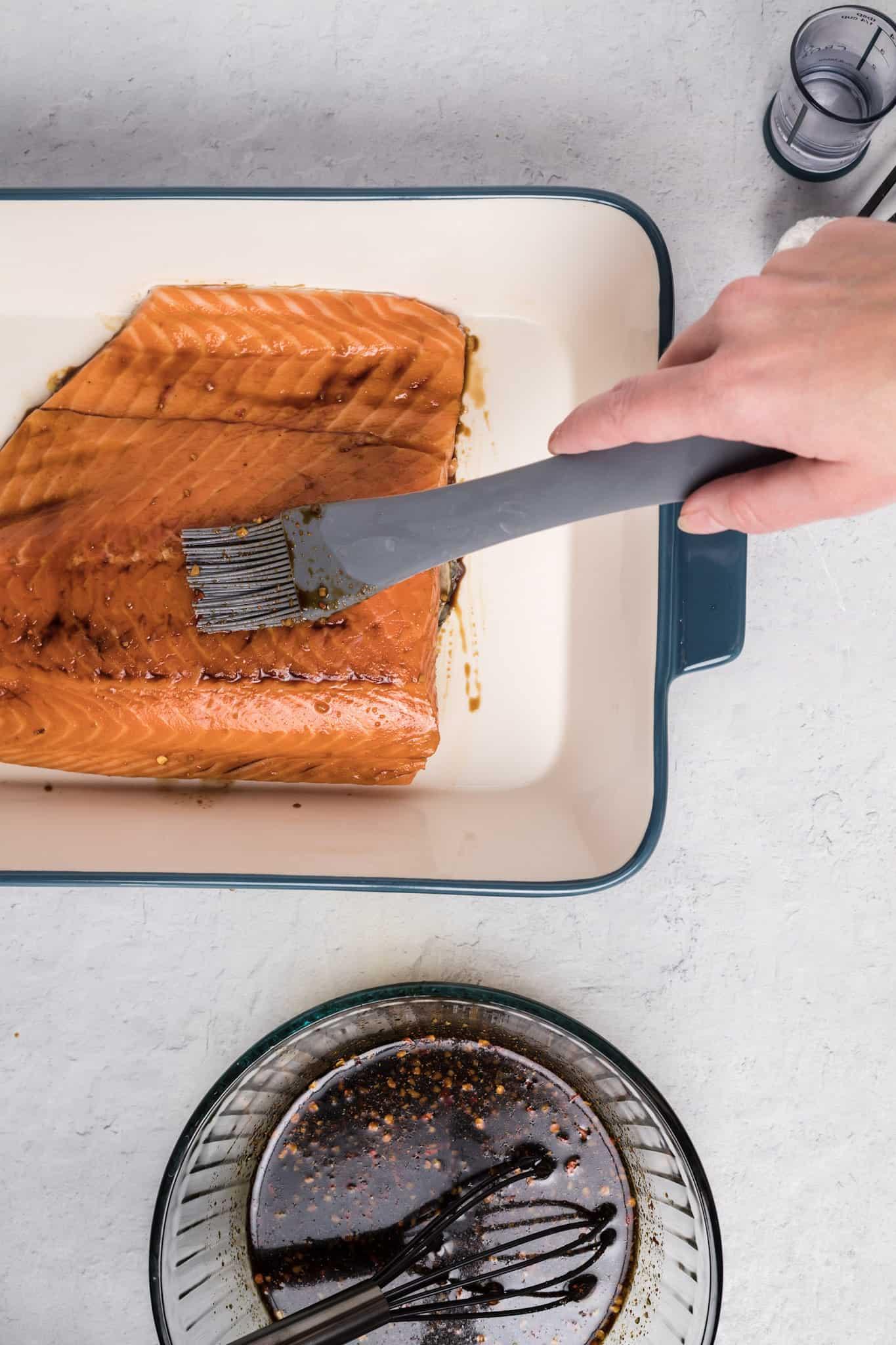Hand brushing glaze over salmon in dish.