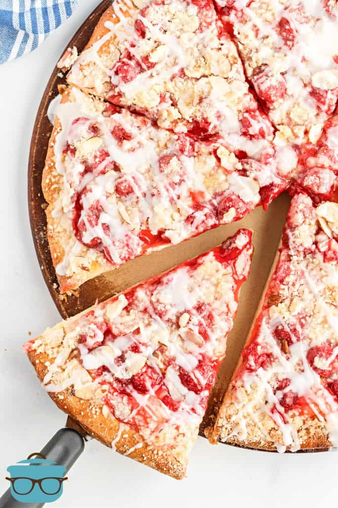 Whole cherry dessert pizza with streusel topping being shown with one slice being slightly removed from the rest of the pizza