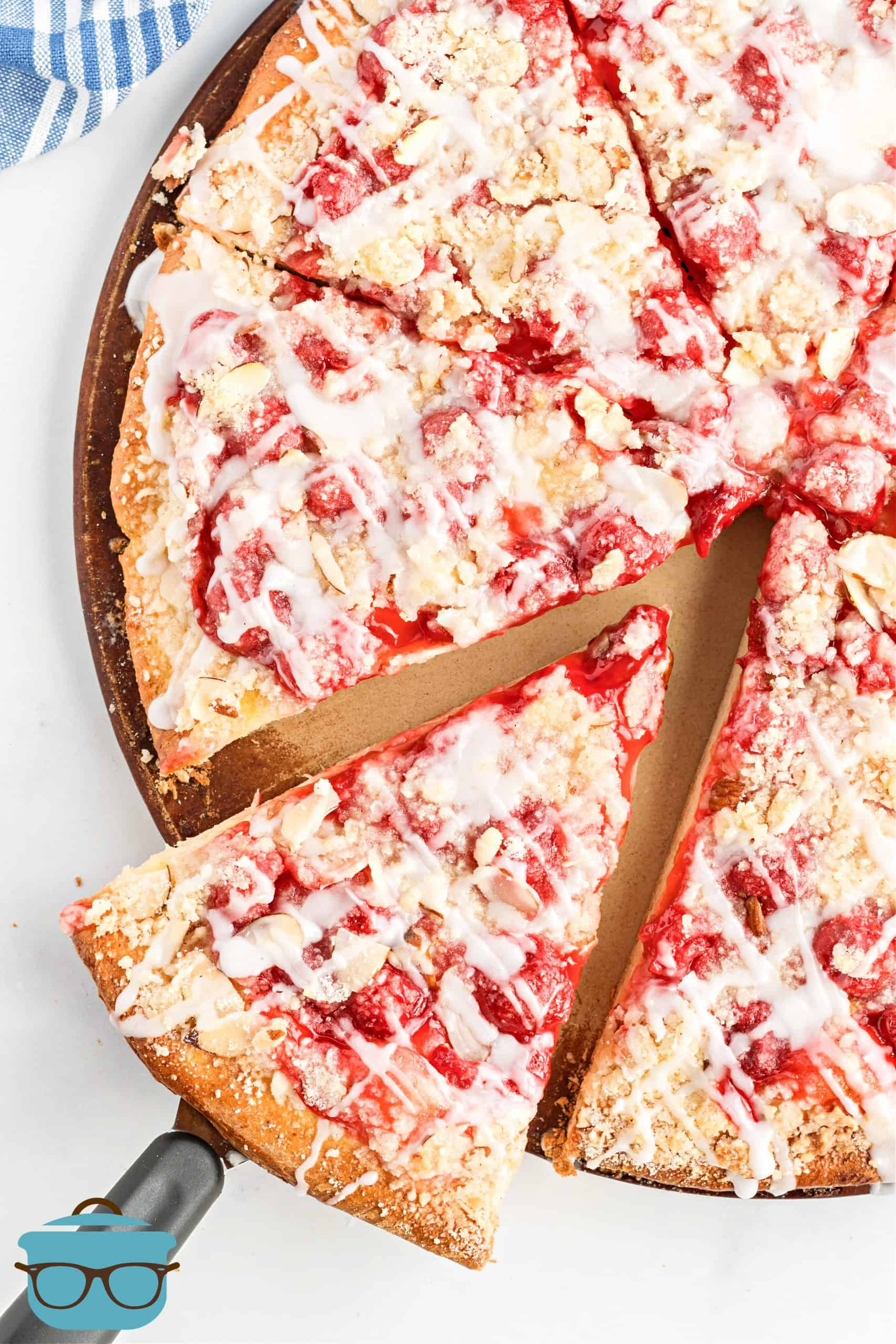 Whole cherry dessert pizza with streusel topping being shown with one slice being slightly removed from the rest of the pizza.