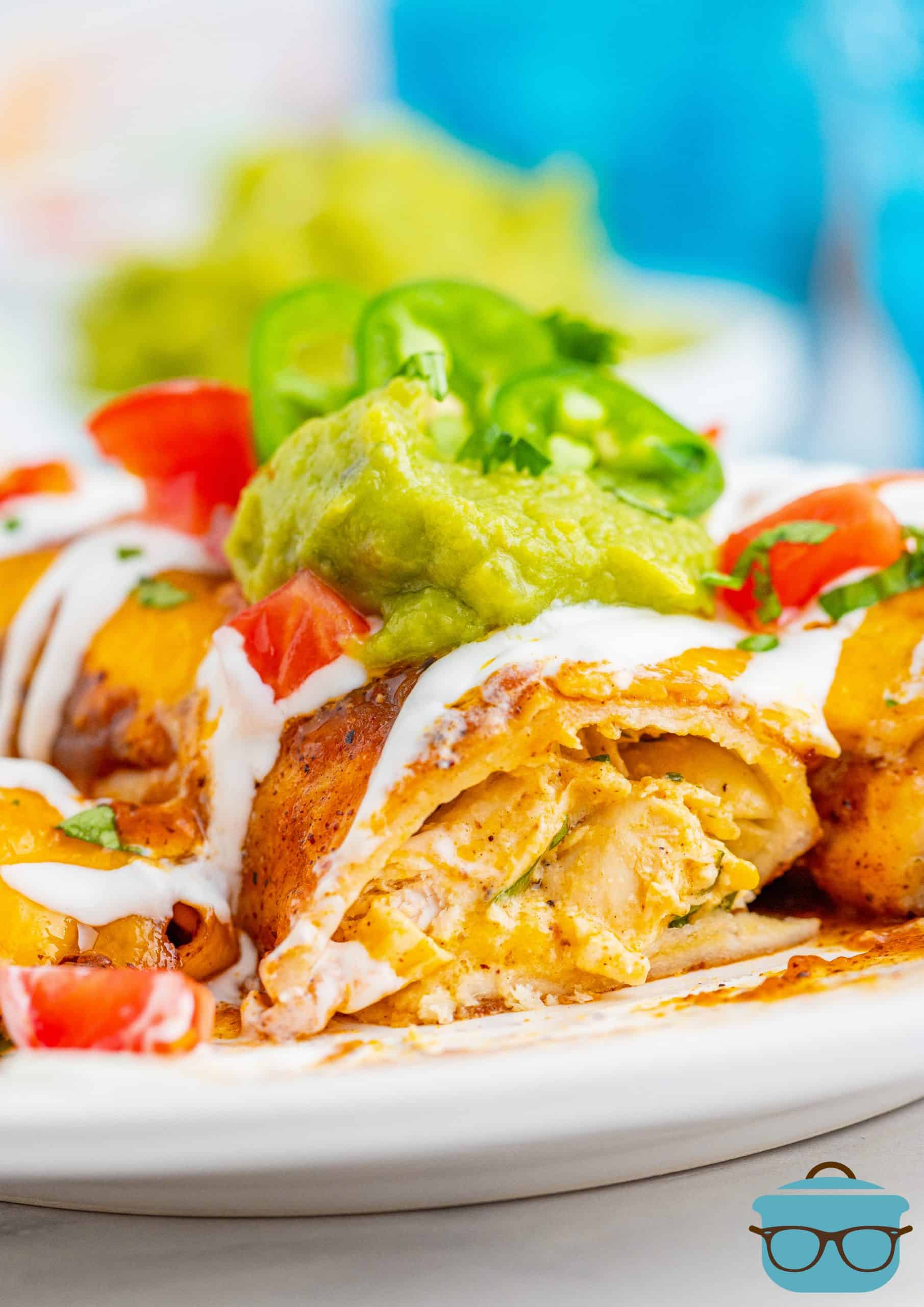 photo showing the inside of the chicken enchilada with guacamole and cream sauce on top.