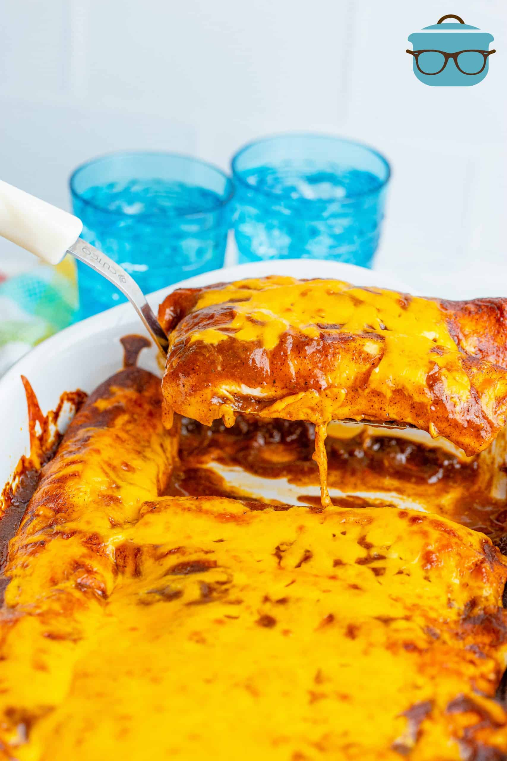 scooping out two red sauce enchiladas out of a baking dish with a spatula.