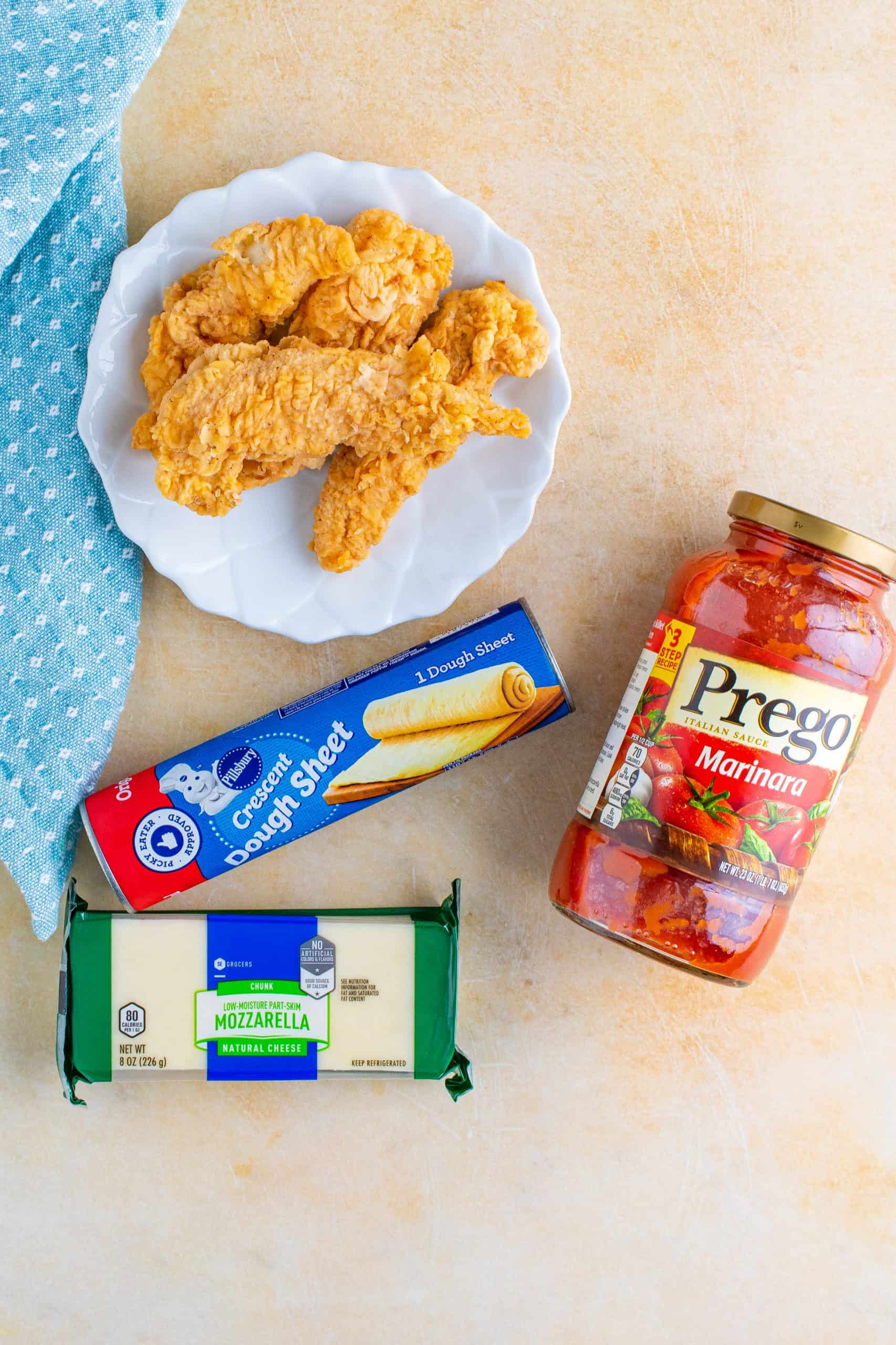 Ingredients needed to make Chicken Parmesan Cups: crescent roll dough sheet, mozzarella cheese, fried chicken tenders, marinara sauce.