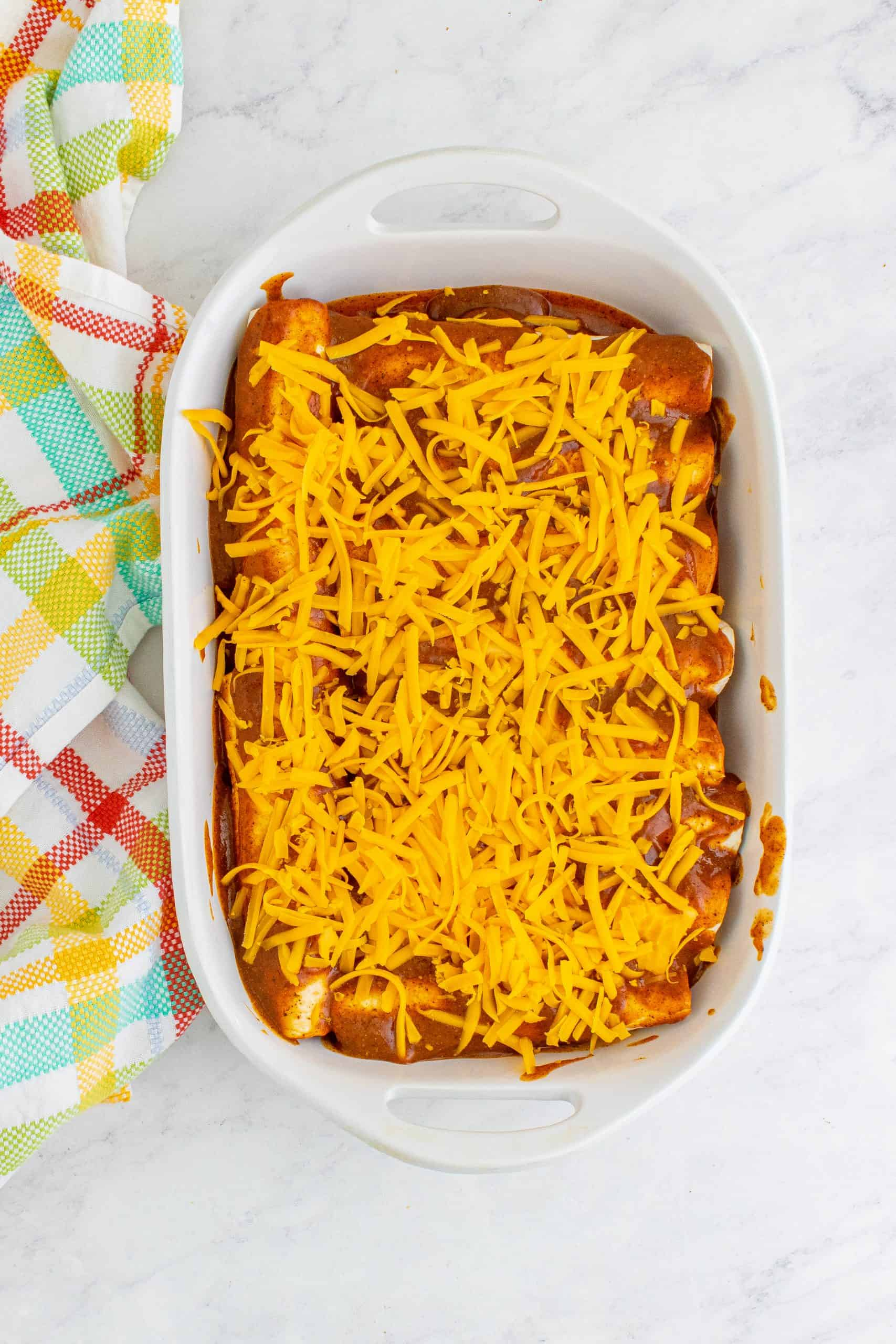 shredded cheddar cheese sprinkled evenly on top of prepared enchiladas in baking dish.