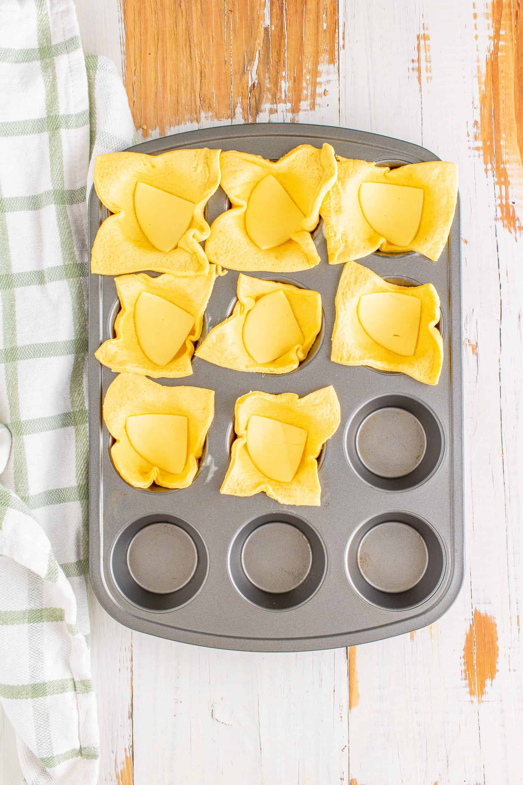 Cheese placed in squares in muffin tin.