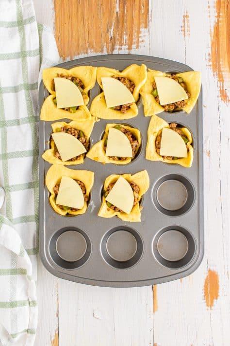 Fatias de queijo colocadas sobre a mistura de carne