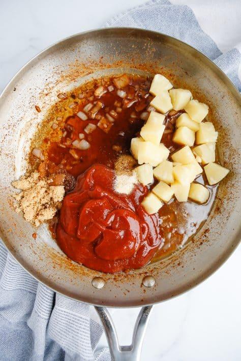 Açúcar mascavo, molho de soja, caldo, açúcar mascavo, alho em pó e pedaços de abacaxi adicionados à panela