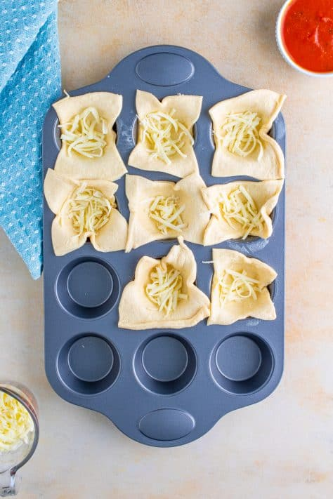 Cheese added to crescent rolls in muffin tin