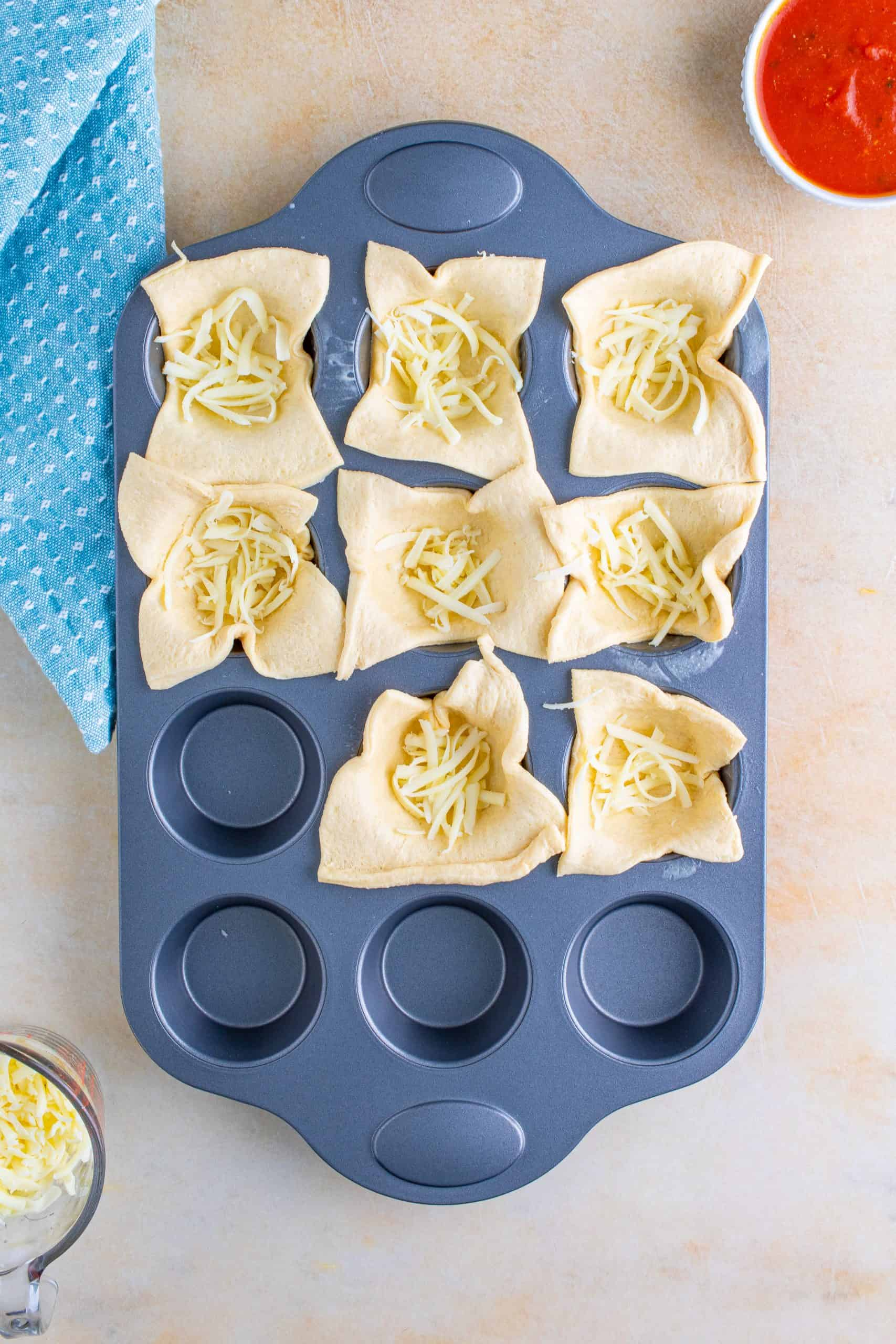Cheese added to crescent rolls in muffin tin.