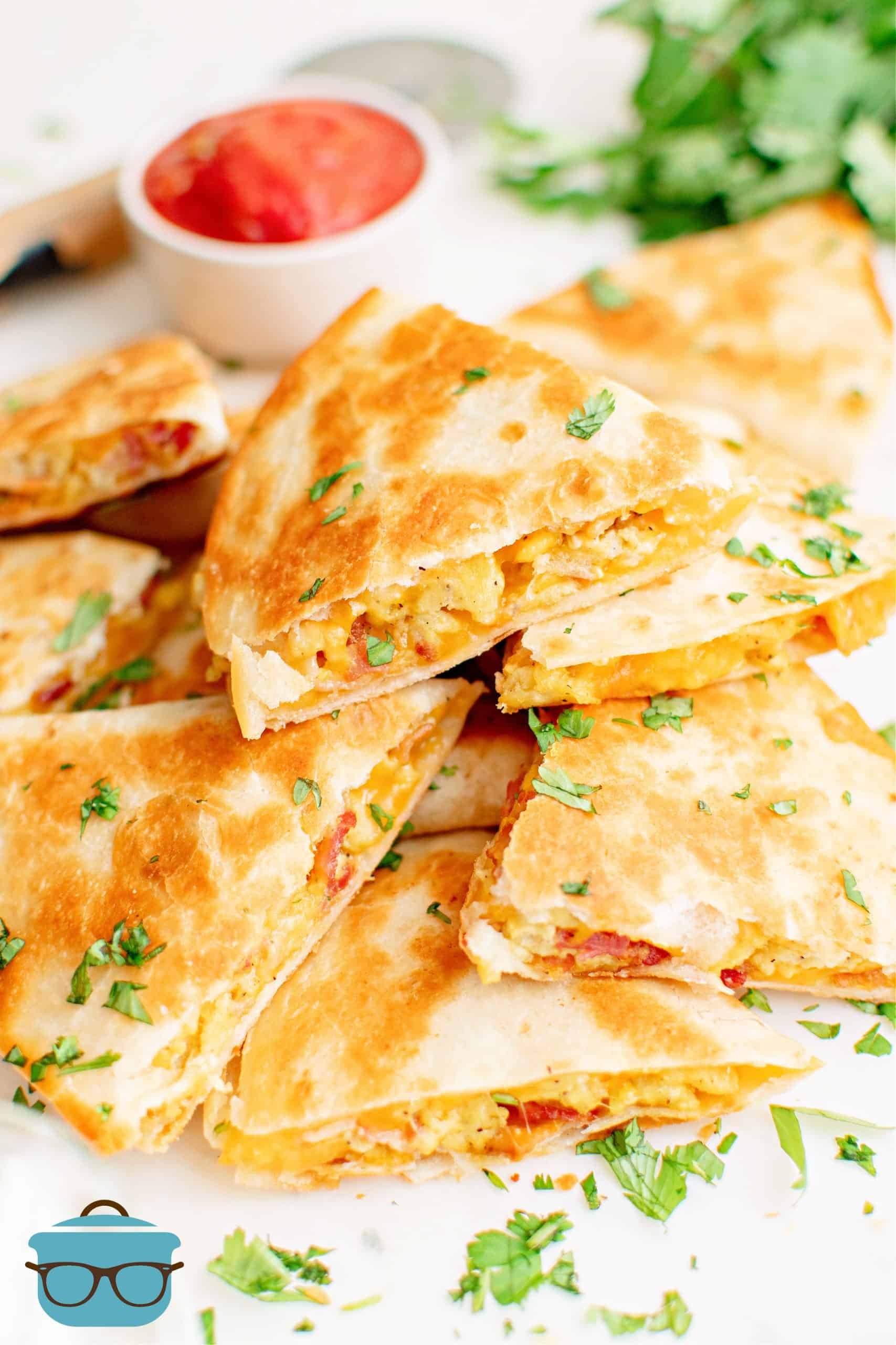 Stacked Breakfast Quesadillas with dipping sauce in background.