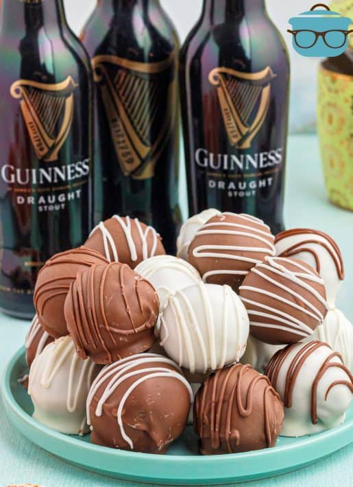 Stacked Guinness Cake Balls on teal plate with bottles of beer in background