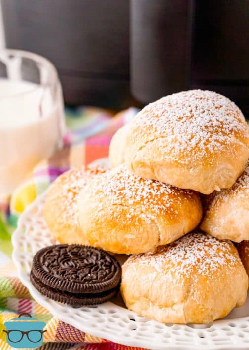 Stacked Air Fryer Fried Oreos on plate topped with powdered sugar close up