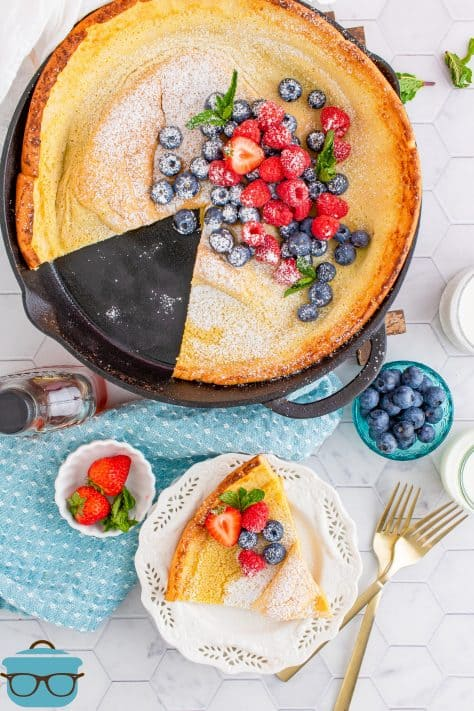 Overhead of a Dutch Baby Pancake with slices taken out of pan on white plate