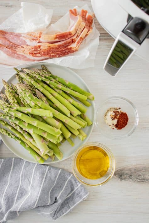 Ingredients needed to make Air Fryer Bacon Wrapped Asparagus: asparagus, olive oil, garlic powder, paprika, salt, pepper, red pepper flakes, bacon