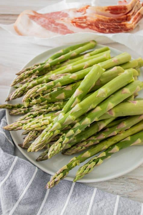 Snapped asparagus pieces on plate with thick cut bacon in the background