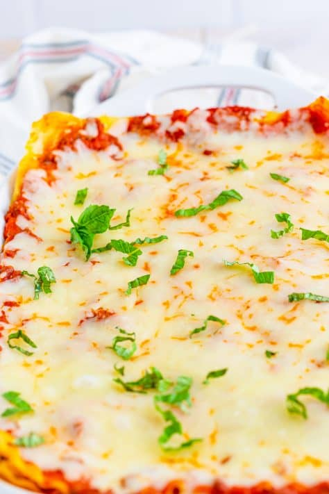 Finished baked lasagna topped with basil close up in pan