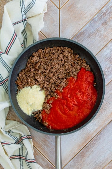 Ground beef, sauce and parmesan in a skillet