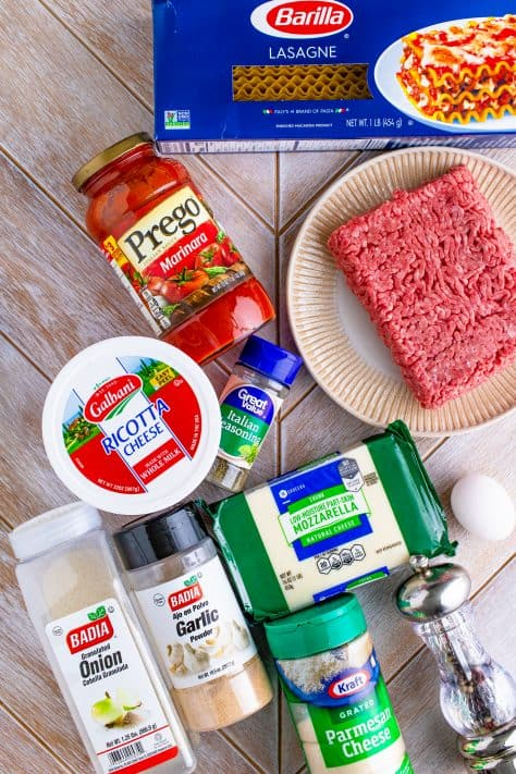 Ingredients needed to make Homemade Baked Lasagna Recipe: ground beef, Italian seasoning, garlic powder, onion powder, pepper, parmesan cheese, marinara sauce, ricotta cheese, egg, mozzarella cheese, lasagna noodles