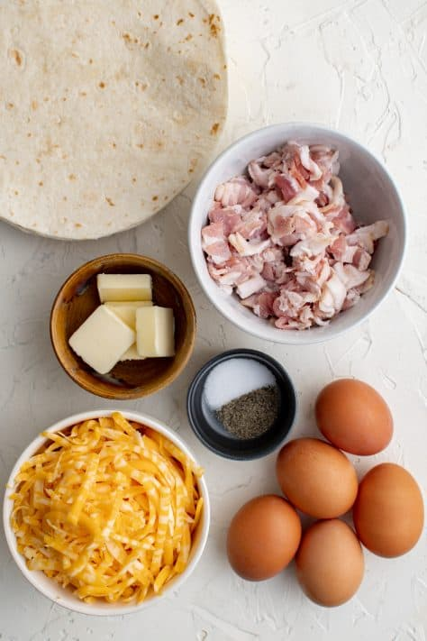 Ingredients needed to make Breakfast Quesadillas: bacon, eggs, pepper, salt, butter, tortillas, cheese