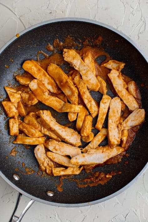 Sliced up chicken in pan