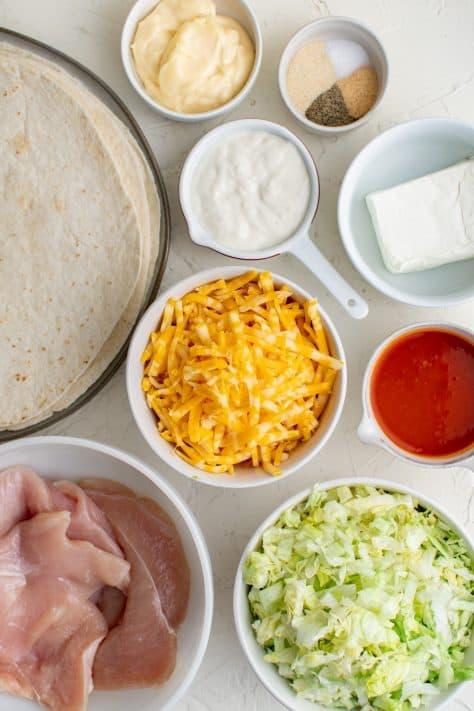 Ingredients needed to make a Buffalo Chicken Wrap: chicken breasts, hot sauce, garlic powder, onion powder, salt, pepper, cream cheese, mayonnaise, blue cheese dressing, tortillas, shredded lettuce, cheese