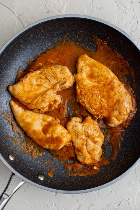 seasoned chicken breasts cooking in a skillet