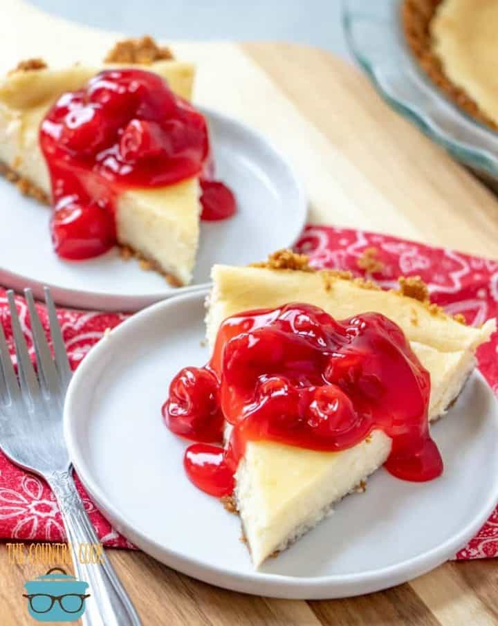 two separate slices of cheesecake on two white round plates. Cheesecakes are topped with cherry pie filling.
