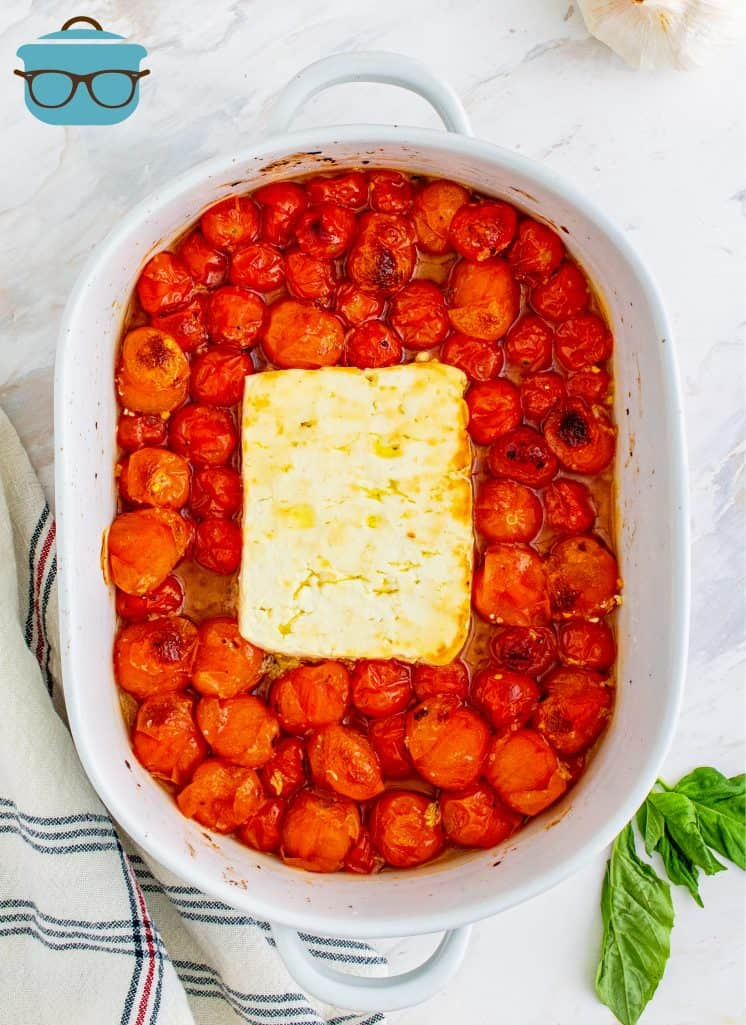 roasted feta cheese and tomatoes shown in an oval white baking dish