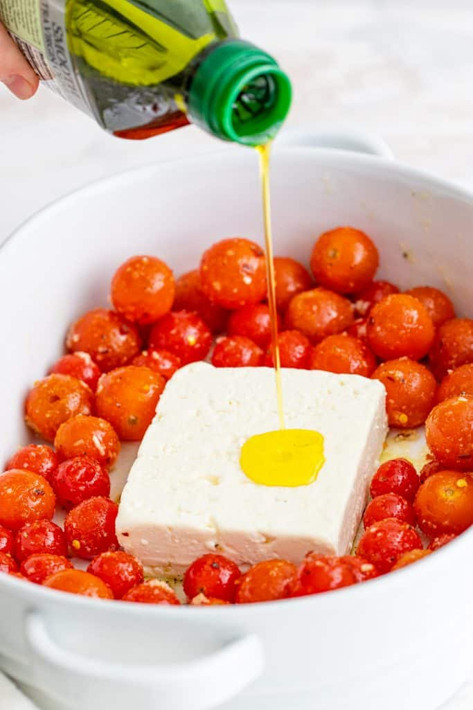 pouring olive oil on top of block of feta cheese and tomatoes in baking dish