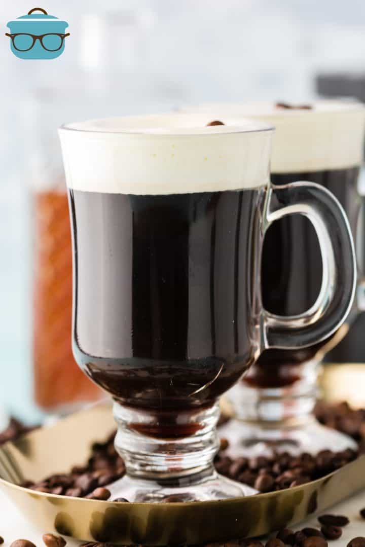 Two mugs of Old-Fashioned Irish Coffee on platter topped with cream