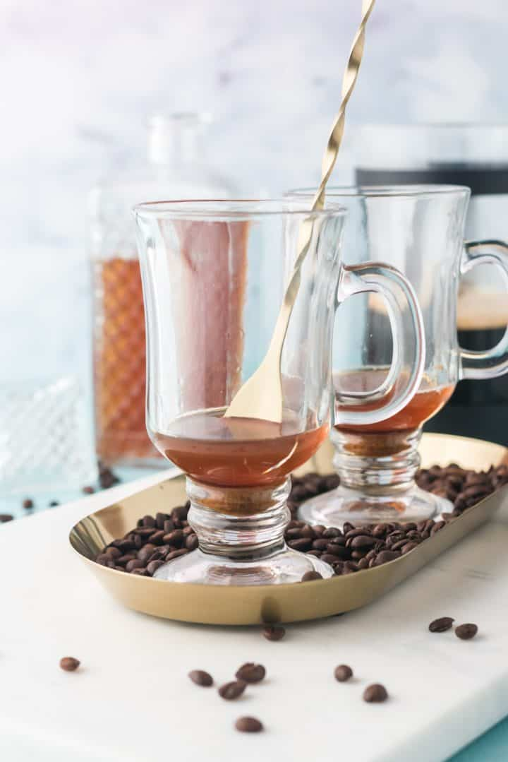 Sugar and whiskey being stirred in mug