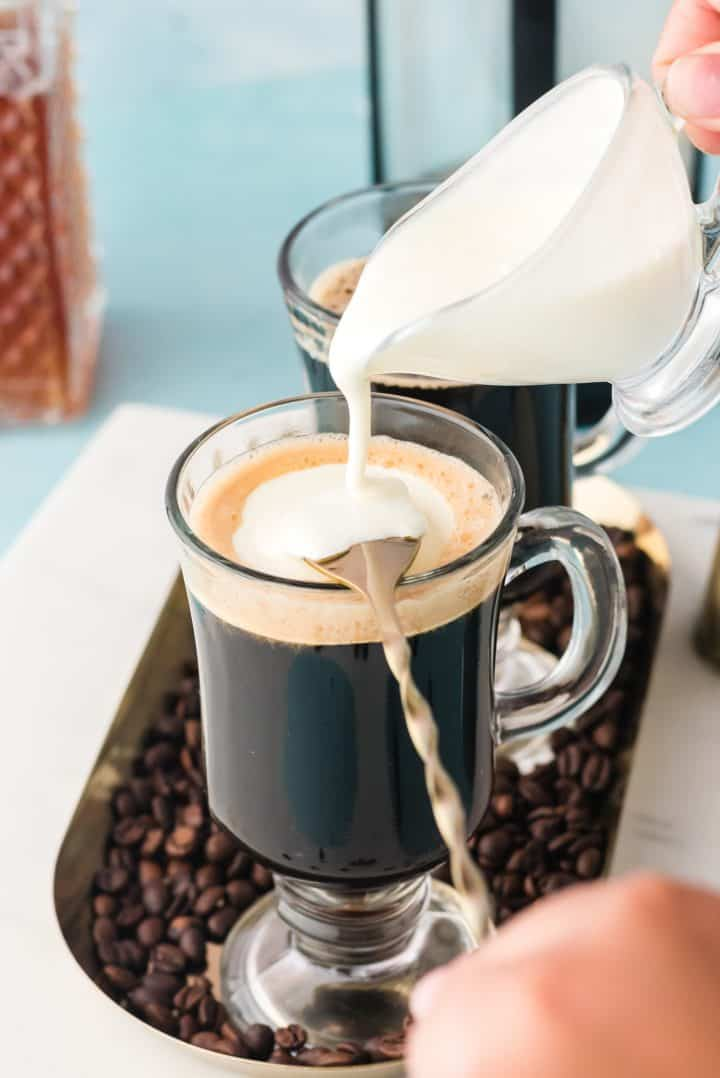 Whipped cream being poured over a spoon into mug over coffee