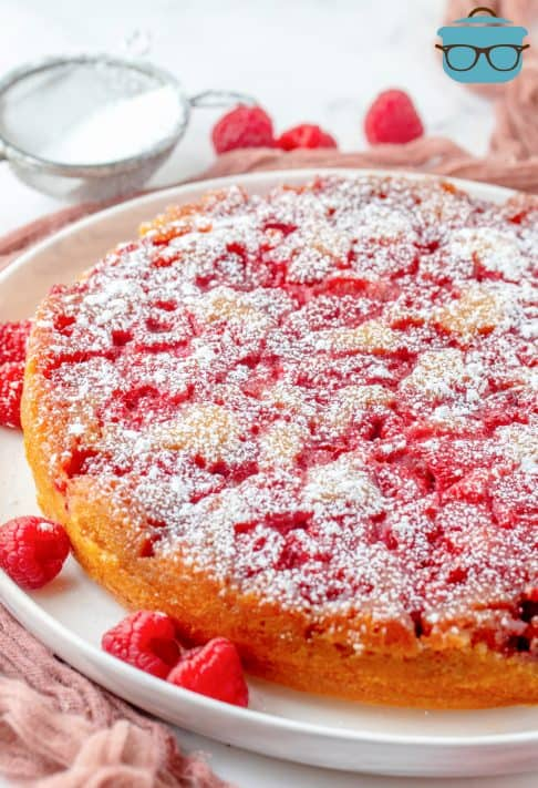Upside Down Raspberry Cake on white platter topped with powdered sugar
